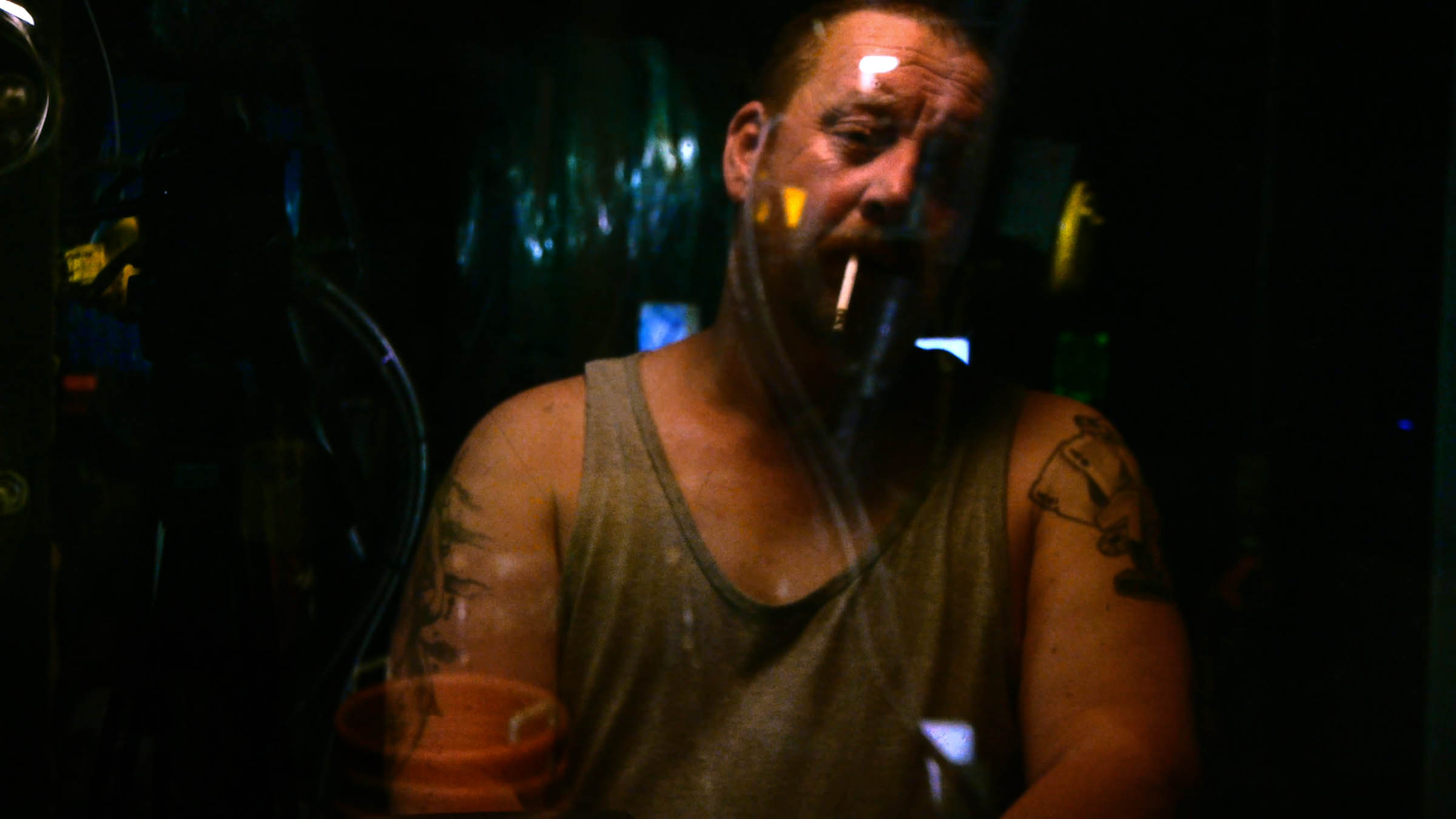 A still from Leviathan. A tattooed man in a grey tank top, seen through glass, works aboard the ship. His head is tilted to the side, his expression shows fatigue, and a cigarette dangles from his lips.