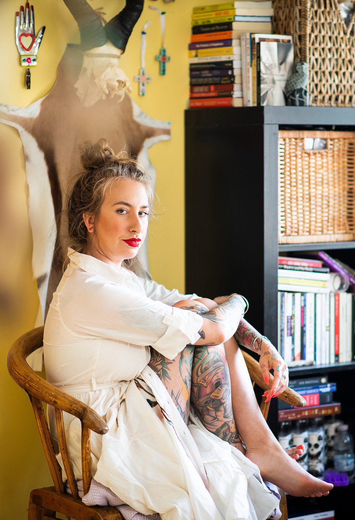 In a loose white gown, the author sits curled up in a chair against a yellow wall, arms folded casually around her knees. Her head is turned to the side and she faces the camera head-on, as if in challenge. There is a laden bookshelf in the background.