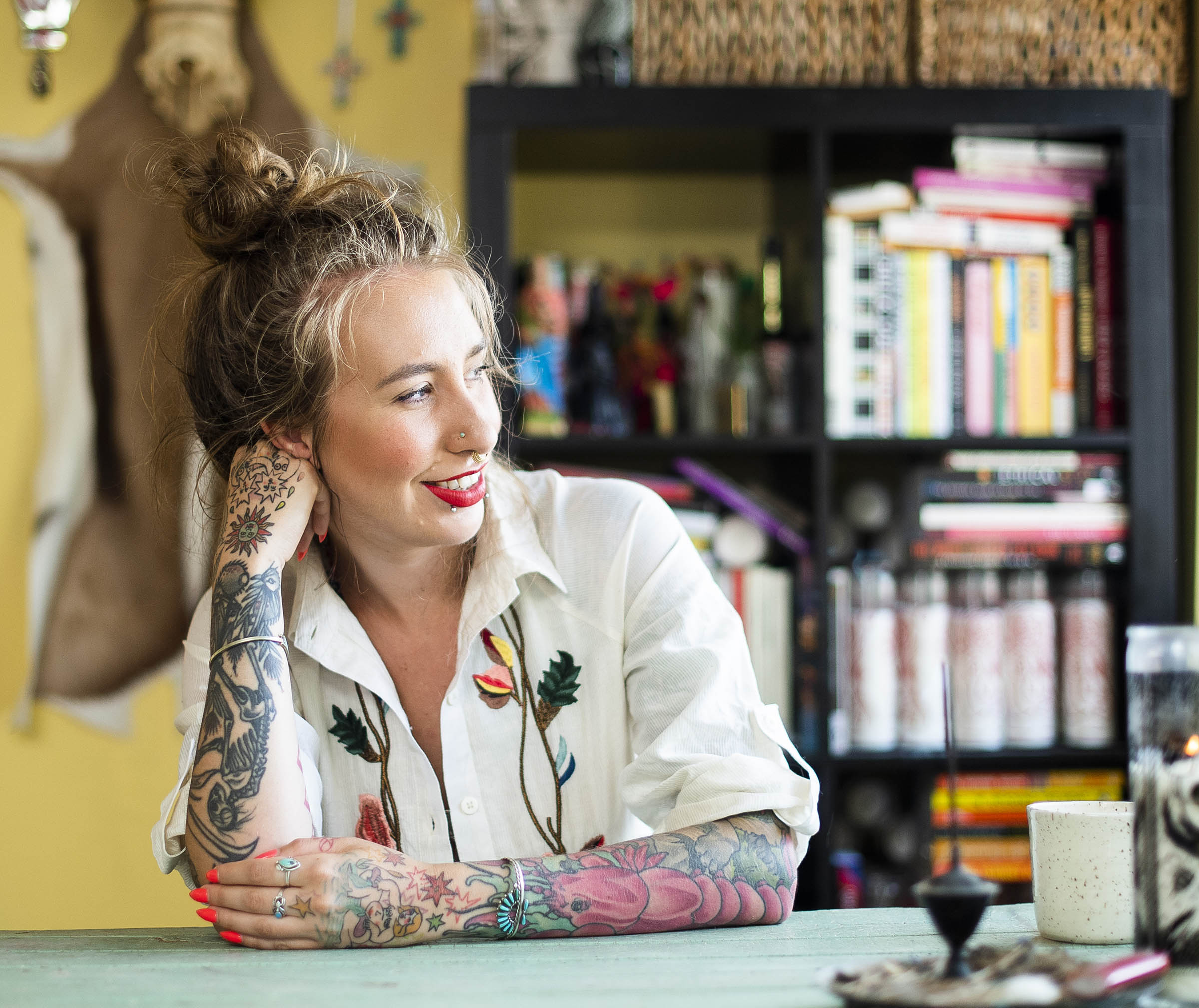 The author sits at a table, smiling at something off to the side. Her hair is up, her fingers and wrists adored with turquoise jewelry. She wears a white shirt with flowers and vines embroidered on it. Behind her, out of focus, is a laden bookshelf, and the skin of a large animal mounted on a yellow wall.