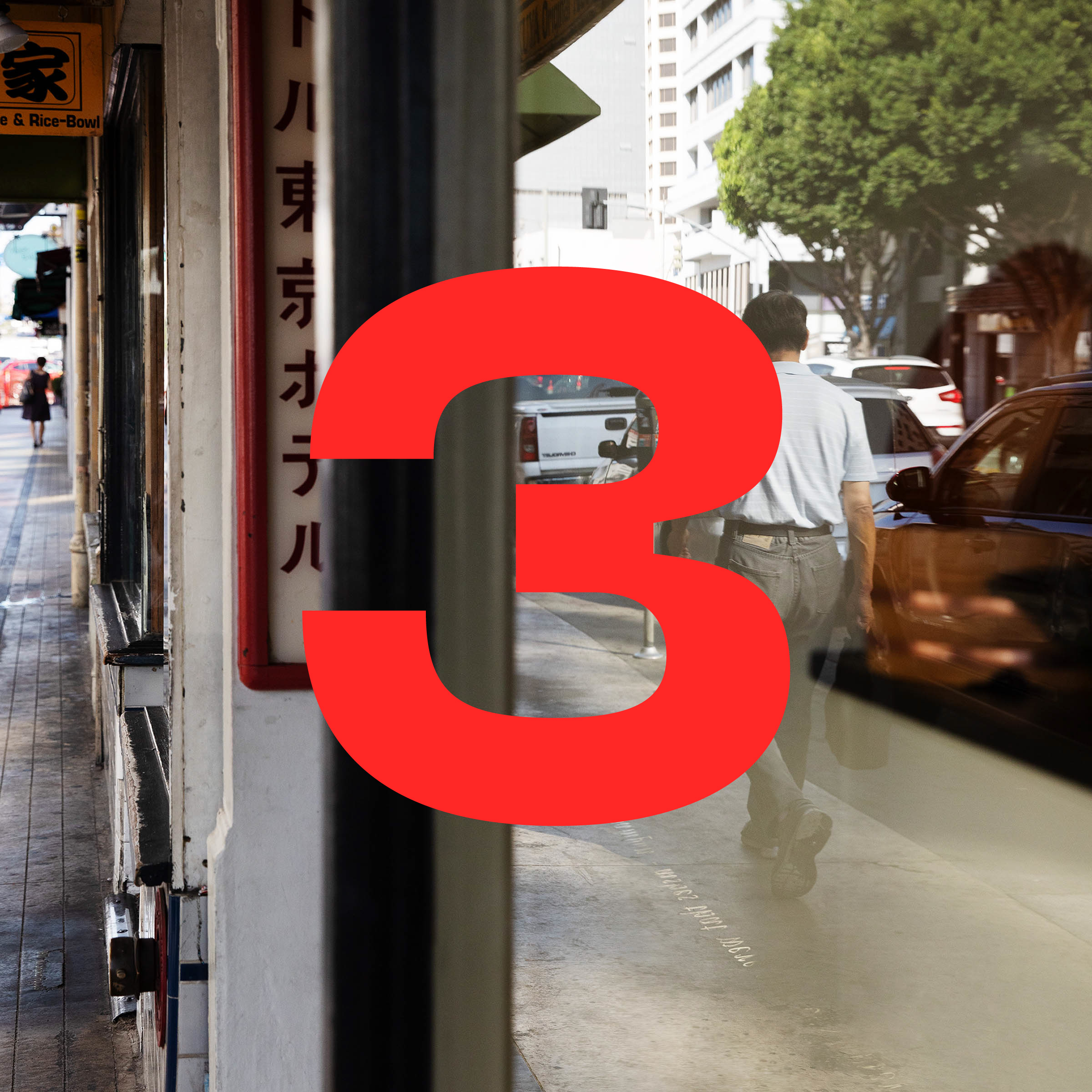 The red numeral 3 is superimposed over a photograph of a city sidewalk. Japanese writing appears on a sign. A shop window reflects traffic, a line of parked cars, and a man walking away from the camera.
